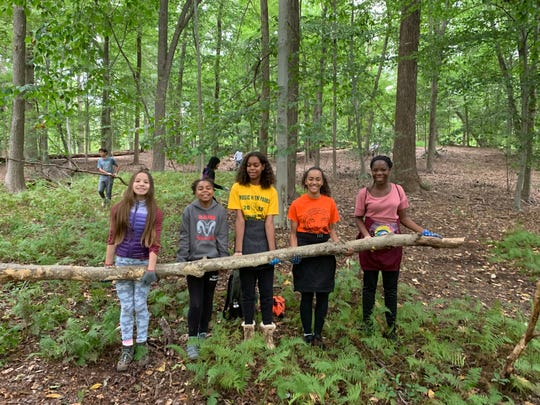 Wardlaw + Hartridge Middle School students Phoebe Kaplan of Scotch Plains, Gabrielle Silver of Rahway, Samia Silver of Rahway, Kayla Martel of Winfield Park and Gbemi Olaweraju of Piscataway carry a heavy branch through the woods.