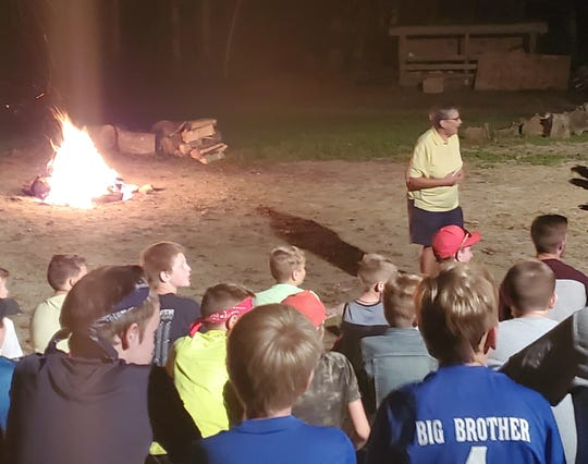 Sandy Knuth, founder of the sixth grade camp for River View Local Schools, returned to the 40th anniversary of the program to speak with students at one of the nighttime camp fires.