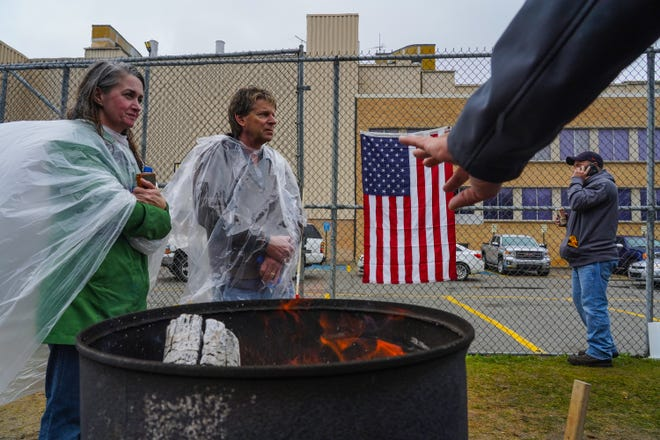 UAW Local 589 members try to warm up while standing in the rain outside of Flint Assembly while on strike against General Motors on Wednesday, October 2, 2019.