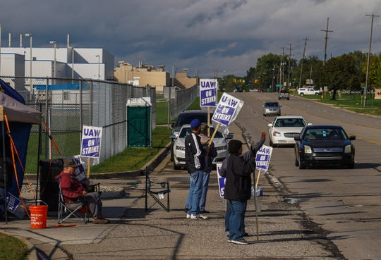 UAW members stand on strike along Van Slyke Rd. in Flint against General Motors outside of the gate for Flint Engine Operations on Thursday, October 3, 2019.