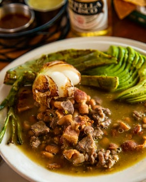 Chopped steak stew with bacon and pinto beans in beef broth served with grilled nopales, grilled onions, and avocadoat El Nacimiento