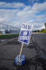 A UAW strike sign is held up by a case of water outside of Flint Engine Operations in Flint on Thursday, October 3, 2019.