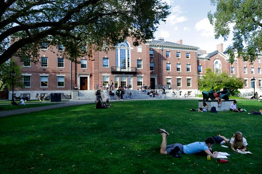 In this Sept. 25, 2019, photo, people rest on grass while reading at Brown University in Providence, R.I. Tax and charity records show that prestigious universities around the world, including Brown, have accepted at least $60 million from the family that owns OxyContin maker Purdue Pharma over the past five years, even as the company has been embroiled in lawsuits over its role in the opioid epidemic.