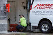 An electrician works at a car wash in North Andover, Mass.