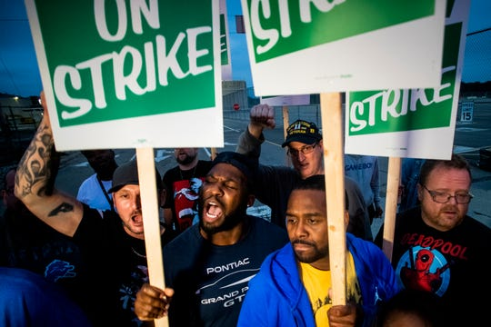 General Motors employees Bobby Caughel, left, and Flint resident James Crump, shout out as they protest, united in solidarity with other GM employees, UAW members and labor supporters outside of the Flint Assembly Plant on Monday, Sept. 16, 2019 in Flint, Mich. Thousands of members of the United Auto Workers walked off General Motors factory floors or set up picket lines early Monday as contract talks with the company deteriorated into a strike. (Jake May/The Flint Journal via AP)
