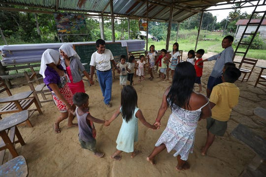"Antelmo Pereira leads a circle of worshippers during catechesis lessons in the Tikuna village of Santa Rosa, Brazil, Saturday, Sept. 21, 2019. ""This is a strict path that not everyone is willing to follow"" Pereira says. ""In my community we need more people to announce the word of God."""