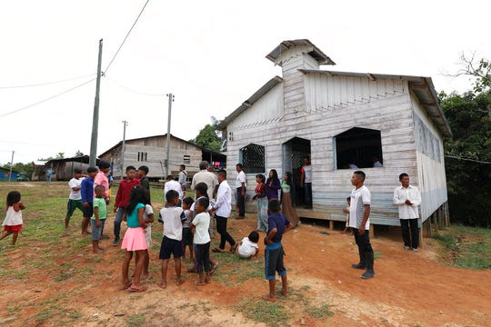 Residents gather outside the Catholic church of Novo Cruzador, Brazil, after attending a prayer led by missionary Antelmo Pereira on Sunday, Sept. 22, 2019. In remote Amazonian communities that are only accessible by boat, villagers can go for months without sacraments that only priests are allowed to deliver - including Mass and confessions.