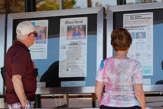 People stop to look at newspaper front pages, from around the U.S., on display at the Newseum in Washington on Sept. 25, 2019.