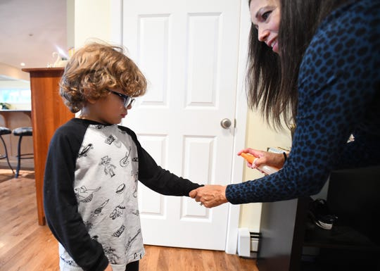 Karen Wile sprays her son Gabe, 6, with bug spray before he goes outside in Vicksburg, Michigan.