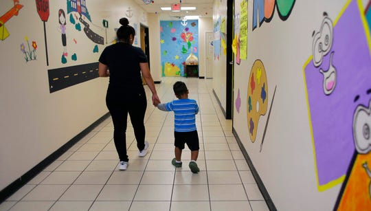 "A young migrant boy walks with a Comprehensive Health Services caregiver at a ""tender-age"" facility for babies, children and teens, in Texas' Rio Grande Valley, Thursday, Aug. 29, 2019, in San Benito, Texas."
