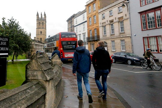 In this Sept. 3, 2017, file photo, people walk around Oxford University's campus in Oxford, England. Oxford, the University of Glasgow in Scotland and Cornell each received $5 million to $6 million, tax records show.