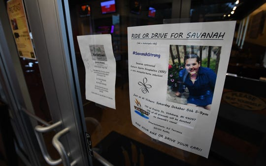 A flyer in the window of Vickers Lakeside Tavern in Vicksburg, Michigan, promotes an event that will donate 10% of the proceeds to help Savannah DeHart, 14, who contracted the EEE mosquito virus.