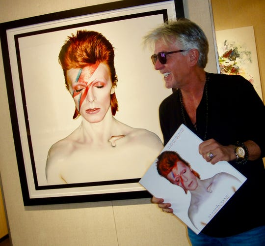 Gerard Marti, owner of Robert Kidd Gallery, with photo artwork of David Bowie.