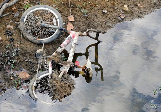 In this Sept. 26, 2019 file photo, a bicycle that was submerged in a pond lies on a dried-up bank in Helena, Ala.