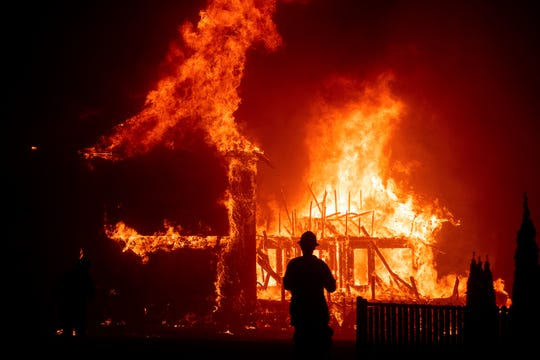 FILE - In this Nov. 8, 2018, file photo, a home burns during a wildfire in Paradise, Calif. Gov. Gavin Newsom has signed, Wednesday, Oct. 2, 2019, nearly two-dozen laws aimed at preventing and fighting the devastating wildfires that destroyed the Sierra foothills city last fall.