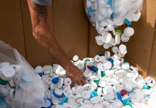 Green Tree Plastics employee Brad Klene reaches into a bin of plastic caps collected by W. E. Sears Youth Center in Poplar Bluff, Missouri who participates in the ABC promise partnership program Wednesday, Sept. 25, 2019. The youth center collected 2030 lb. of plastic caps.
