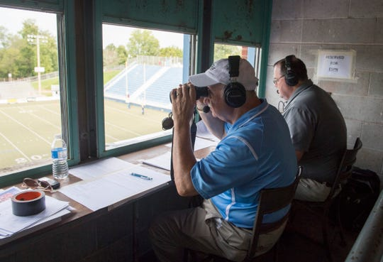 Mike Skvara, left, peers down at the field through binoculars as him and Ryan Wagler announce the Mater Dei vs Whiting football game at the Reitz Bowl for  ESPN Radio WREF Saturday, Aug. 31, 2019.