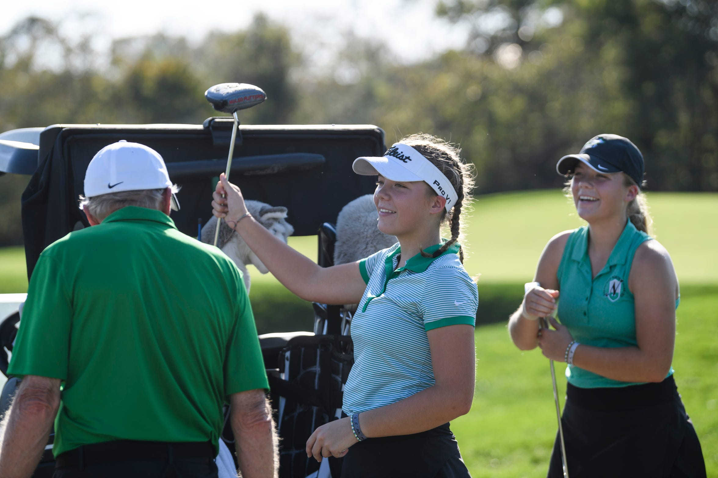 North Girls' Golf Coach Ken Wempe, from left, jokes around with sophomore twins Faith and Chloe Johnson during practice at Victoria National Golf Club in Newburgh, Ind., Wednesday afternoon, Oct. 2, 2019. The team will compete for another state championship at Prairie View Golf Club in Carmel, Ind., this weekend.