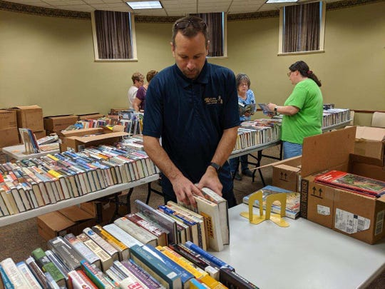 Steve Monticue of Friends of the Clyde Library stacks books for the weekend book sale.