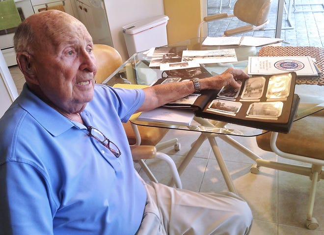 Sid Harris looks over a book of photographs from his World War II experience as a B-17 bomber pilot. Harris got a chance to fly on the B-17 in 2015. The plane crashed Wednesday in Connecticut, killing seven.