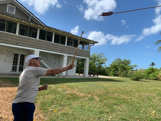 Fort Myers resident Layne Prebor throws an atlatl during a hands-on presentation of the technology used by the Calusa next to the Mound House in Fort Myers Beach, Oct. 2, 2019.