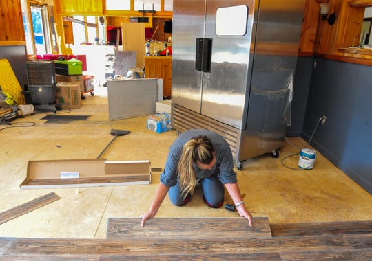 Hayley Mieyr lays down new floor at the Missouri River Inn Restaurant and Bar at Hardy Creek.  Mieyr and her daughter Schuler Mieyr are the new owners and hope to reopen the bar and restaurant early next year.