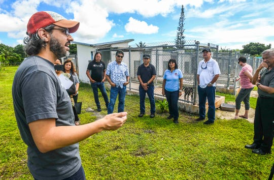 Guam Animals In Need President Cyrus Luhr, front, explains some of the financial challenges to  island village leaders during a tour around the non-profit animal shelter in Yigo on Thursday, Oct. 3, 2019.