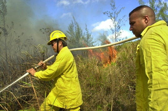 In this April 2002 file photo, Lt. Rudy Paco, left, and firefighter Mark Cummins, of the ComNavMar Fire Department battle a brush fire in Santa Rita. Paco, who now is mayor of Mongmong-Toto-Maite is one of nearly two dozen former and current firefighters who this week filed a lawsuit related to their exposure to firefighting chemicals.