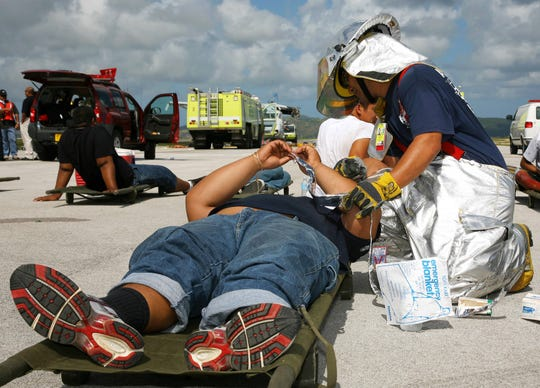 In this June 2008 file photo, GIAA firefighter Michael Roberto treats a mock crash victim during a disaster drill conducted by the A.B. Won Pat International Airport Authority. Roberto, who still is an airport firefighter, is one of nearly two dozen former and current firefighters who sued this week over their exposure to firefighting chemicals.