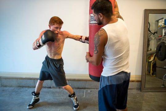 Alex Maldonado, left, trains with the help of his father Daniel Maldonado, right, in their home garage in Henderson, Ky., Wednesday evening, Oct. 2, 2019. Daniel fought professionally from 2000 through 2008 and won the International Boxing Association's world title in 2006.
