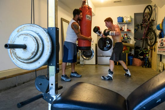 "Daniel Maldonado, left, holds the punching bag for Alex Maldonado as they run drills in their home garage in Henderson, Ky., Wednesday evening, Oct. 2, 2019. ""He's following in my footsteps,"" Daniel said. ""But he's a lot more focused than me."""