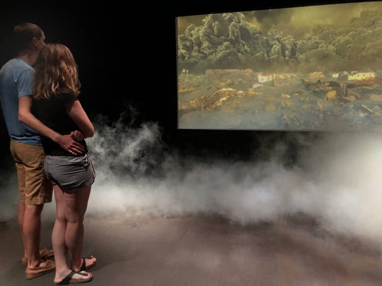 A couple watches a computer-generated portrayal of suffocating ash and lava descending on ruined Pompeii while simulated smoke rises in the Saint Louis Science Center's 4-D Eruption Theater.