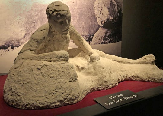 The haunting image of a person's last gasping moments was captured once a victim was covered in wet ash that hardened into a shell that became a mold for this plaster cast, centuries after the person's remains inside had decayed.