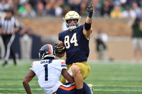 Notre Dame Fighting Irish tight end Cole Kmet (84) celebrates after a catch in the second quarter as Virginia Cavaliers cornerback Nick Grant (1) defends at Notre Dame Stadium.