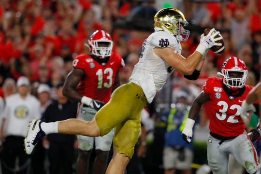 Cole Kmet #84 of the Notre Dame Fighting Irish catches a second quarter touchdown in front of  Monty Rice #32 of the Georgia Bulldogs at Sanford Stadium on September 21, 2019 in Athens, Georgia.
