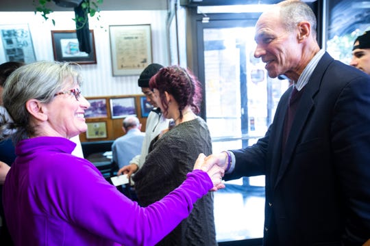 """Rt. Admiral Mike Franken, a Democrat running for U.S. Senate in Iowa, is greeted by Katie Lammers, of Iowa City, Thursday, Oct., 3, 2019, at Hamburg Inn No. 2 in Iowa City, Iowa. Lammers gifted Franken a purple """"resistance bracelet."""""""