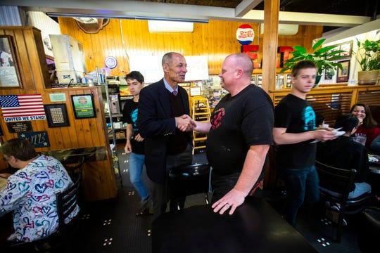 Rt. Admiral Mike Franken, a Democrat running for U.S. Senate in Iowa, shakes hands general manager Seth Dudley, Thursday, Oct., 3, 2019, at Hamburg Inn No. 2 in Iowa City, Iowa.