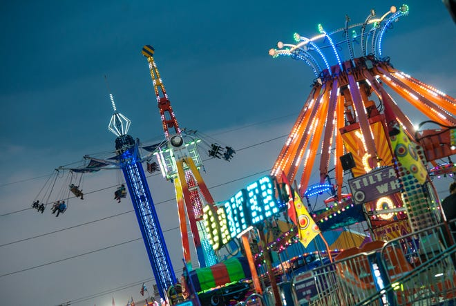 A deep blue sky of dusk is the backdrop for the brightly colored lights opening night at the Mississippi State Fair Wednesday, Oct. 2, 2019. The fair continues through Monday, Oct. 14.