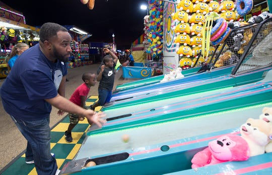 Marcus Brown, of Canton, from left, plays skee ball with his grandsons Khamaree Hicks, 6, and Kamron Williams, 6, also of Canton, during the opening night of the Mississippi State Fair, Wednesday, Oct. 2, 2019.