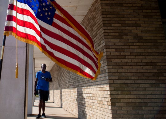 An American Flag waves in front of Curtis Jackson as he walks into the Central Christian Church building to vote for his local candidate in Memphis, Tenn., Thursday, Oct. 3, 2019.