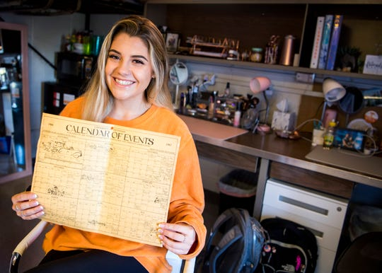 Alex Anastasi, a freshman at the University of Tennessee, sits in her dorm room Thursday, October 3, 2019, with a UT calendar from the 1966-1967 school year she found behind a shelf.