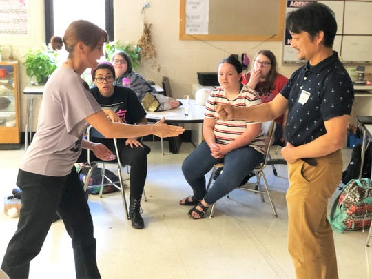 South-Doyle Middle School teacher Jennifer Sauer and Japanese Club guest Shigetoshi Eda demonstrate a Japanese game for the students.