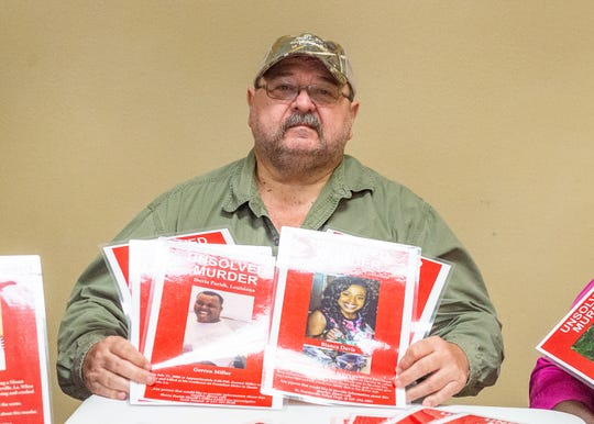 Stephen Menard, who founded the  Justice For Unsolved Murder Victims/Missing Person Project, holds posters of missing people and unsolved murders from Vermilion, St. Martin and Iberia parishes on Thursday, Oct. 3, 2019.