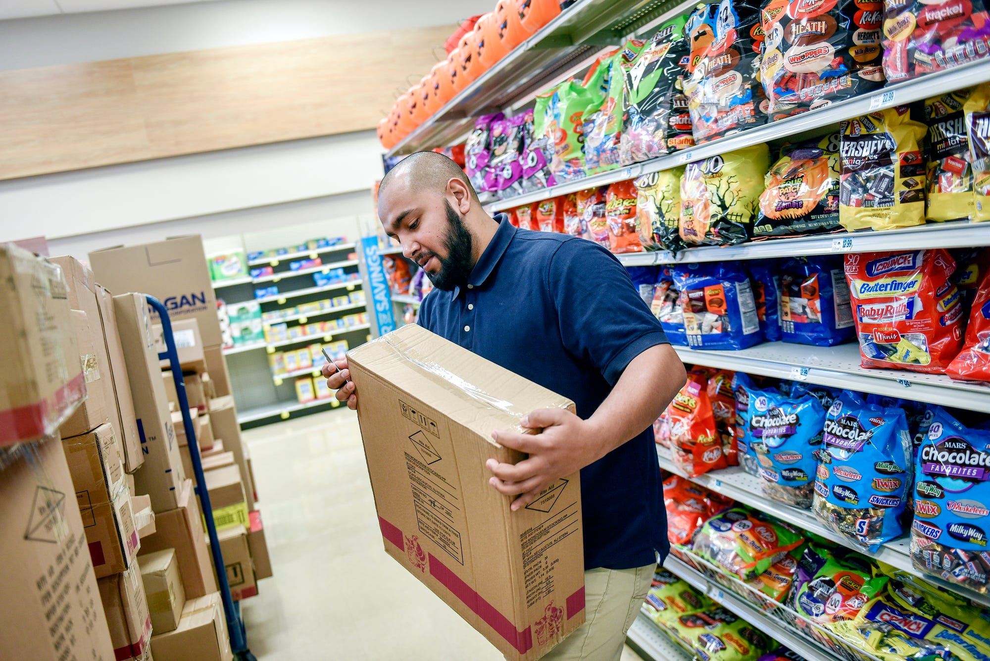 Benito Flores, 25, works on unpacking boxes for another employee while working a shift on Thursday, Oct. 3, 2019, at the Rite Aid in East Lansing. Flores is working two jobs to help out with his $10,000 in student debt.