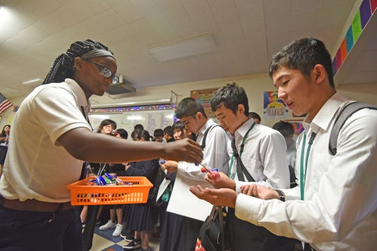Katherine Bryant passes out gifts to visiting students from Japan on Thursday during their visit to St. Peter's School.