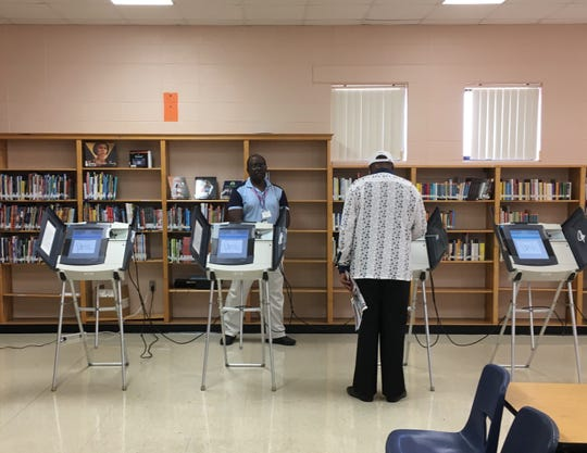 A voter casts his ballot inside the library of Havenview Middle School