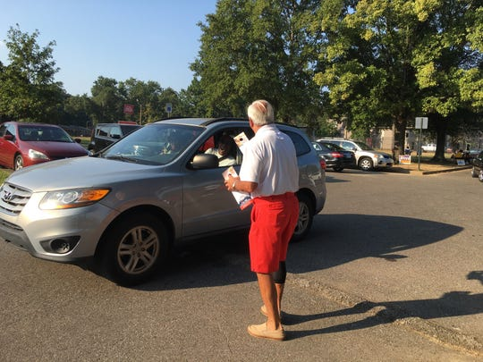 Firefighters union leader Tommy Malone (red shorts) passes out a brochure to a voter as he campaigns for the sales tax referendum outside the Whitehaven Community Center on election day, Thursday, Oct. 3, 2019.