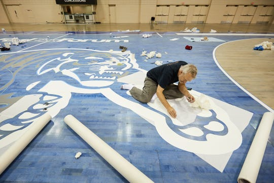 Paul Clements works on the Memphis Tigers men's basketball team's new floor, which was unveiled at Memphis Madness Thursday.