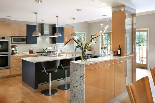 Sleek cabinet and drawer pulls and industrial-like lighting fixtures, range hood and island sink fixtures are integral design elements in this Ulrich kitchen.