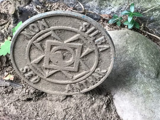 Detail of the Ku Klux medallion at the base of a Mallinson family monument.